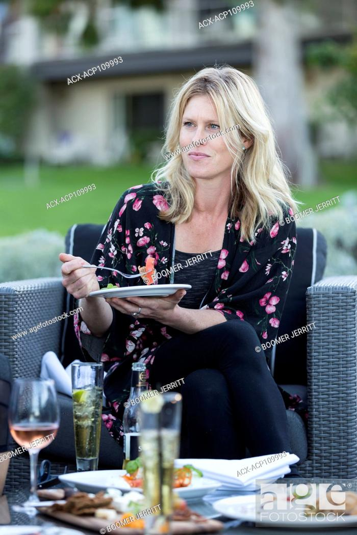 Imagen: An attractive woman relaxes at an outdoor patio with food and drink while visiting the Kingfisher resort in Courtenay. Vancouver Island, British Columbia.