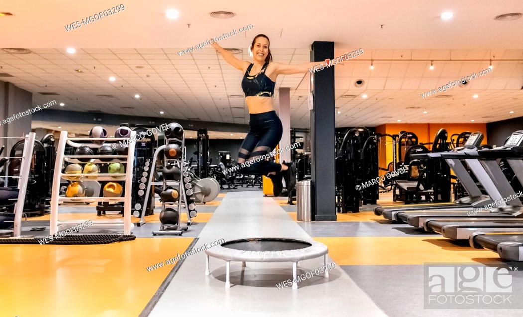 Stock Photo: Young woman jumping in the gym.