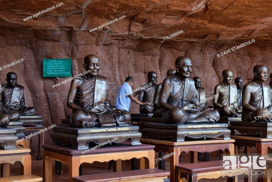 Stock Photo: Man cleaning monk statues at Wat Phu Tok, the mountain top temple in Beung Kan Province, Thailand.
