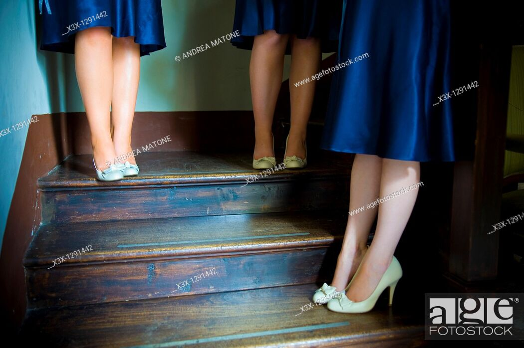 Stock Photo: Cropped view of bridesmaids in blue satin dresses standing on stairwell.