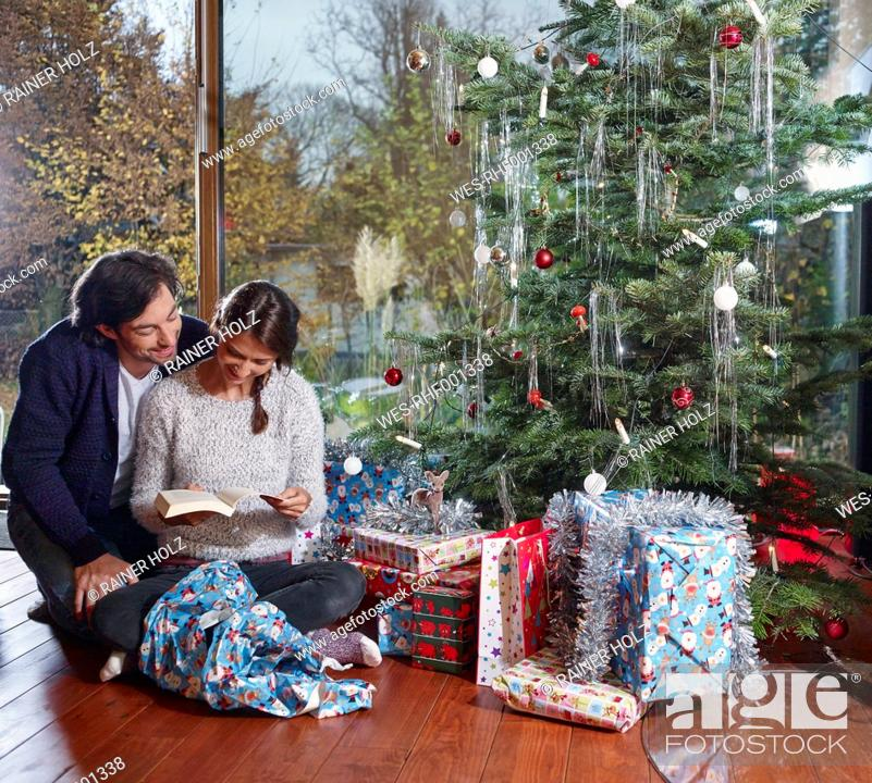 Stock Photo: Couple reading book under Christmas tree.