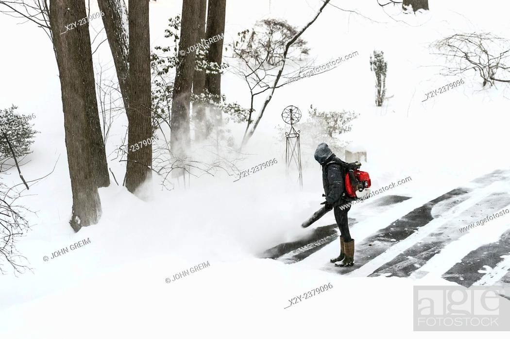 Stock Photo: Woman clears driveway snow with a leaf blower.