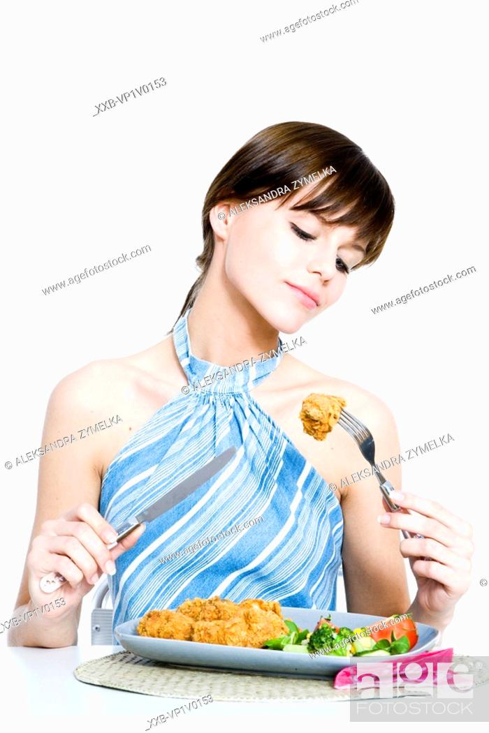 Stock Photo: young woman eating dinner.