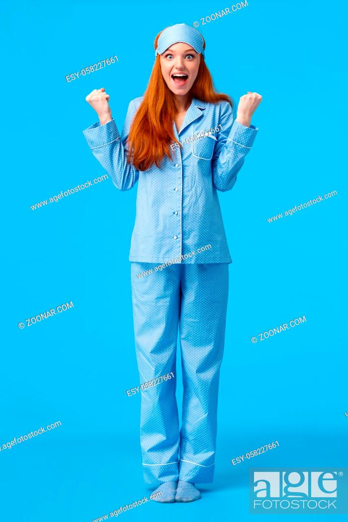 Stock Photo: Luck, happiness and victory concept. Vertical full-length studio shot cheerful triumphing redhead female in nightwear fist pump and smiling saying yes.