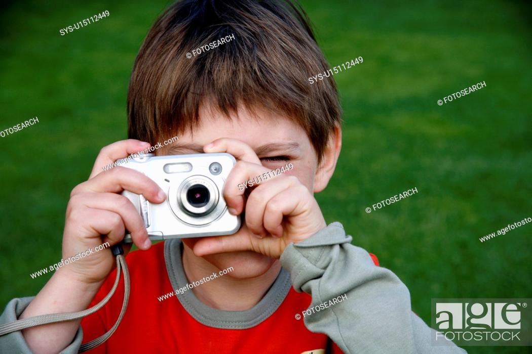 Stock Photo: Little boy holding a camera.