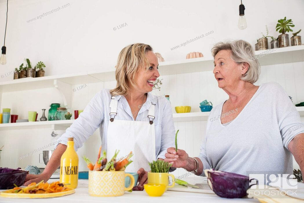 Stock Photo: Senior woman and daughter chatting while preparing vegetables at kitchen table.
