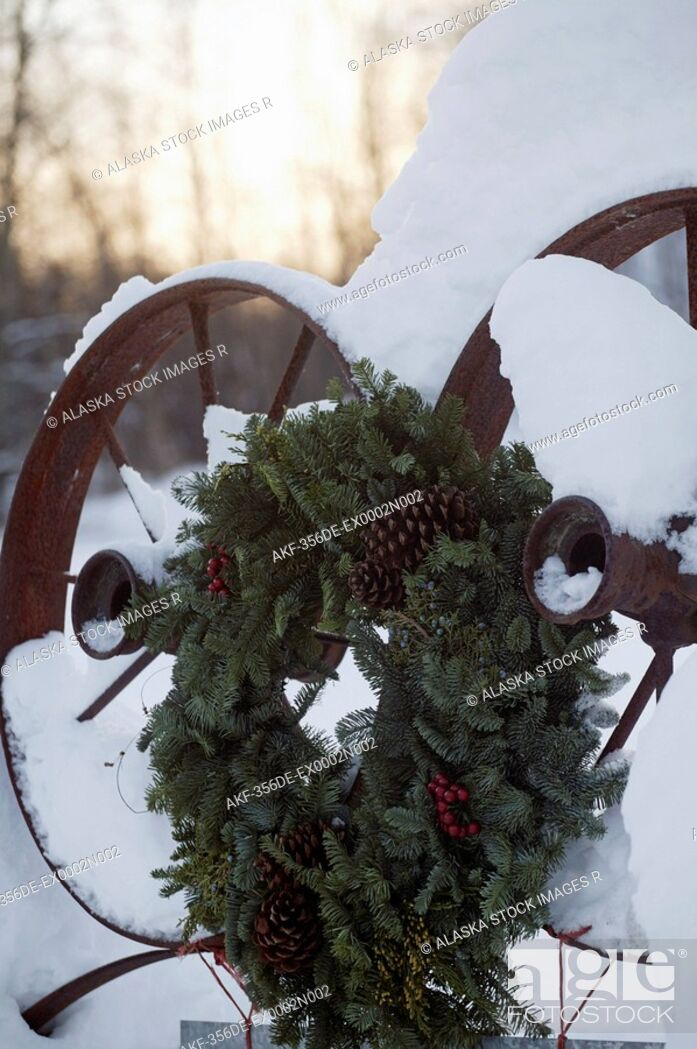 Stock Photo: Holiday wreath hanging on snow covered farm equipment Mat-Su Valley Southcentral Alaska Winter.