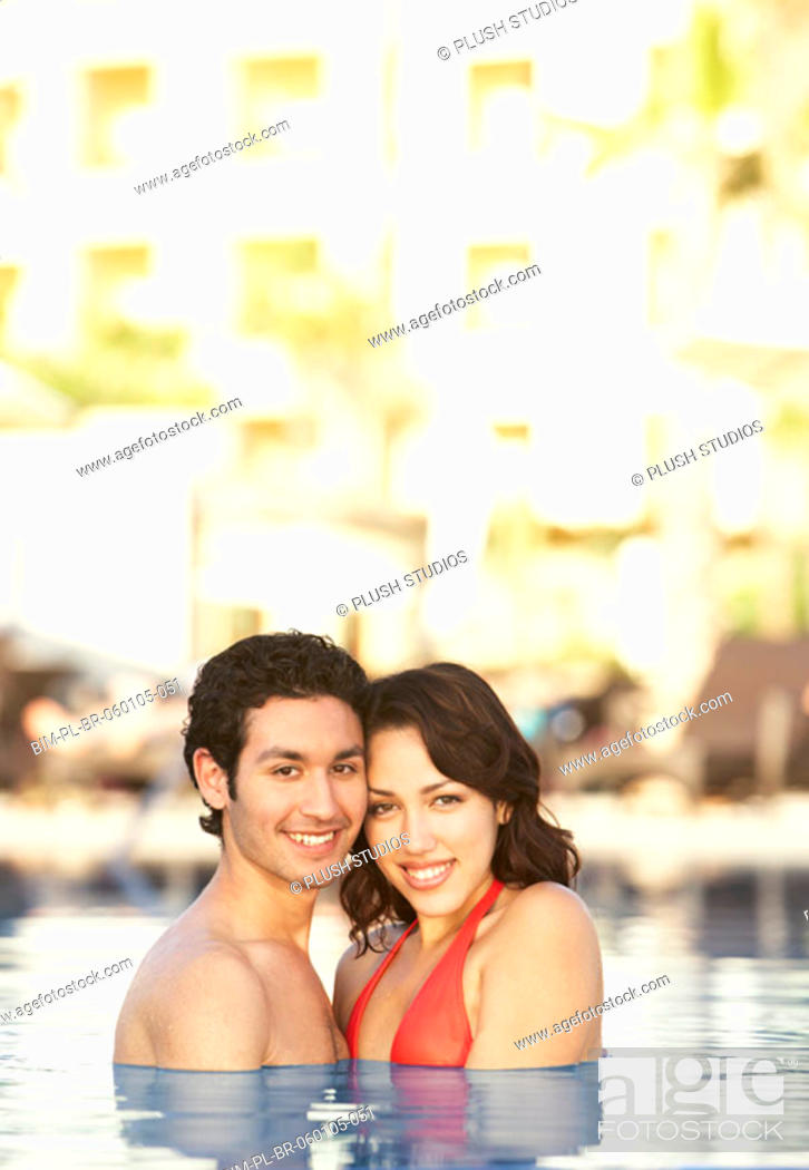 Stock Photo: Young Hispanic couple in a pool, Los Cabos, Mexico.
