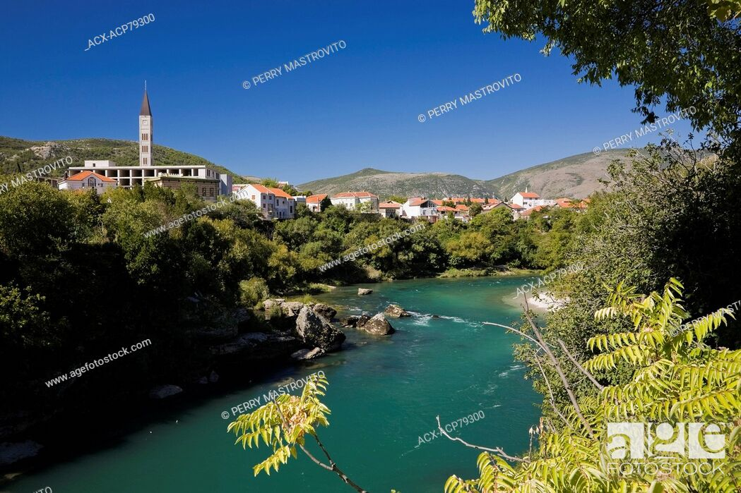 Stock Photo: Neretva river with the bell tower of the St. Peter & St. Paul church and residential homes, Mostar, Bosnia and Herzegovina, Eastern Europe.