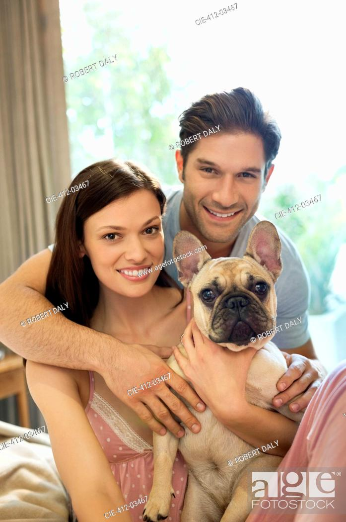 Stock Photo: Couple hugging dog on bed.
