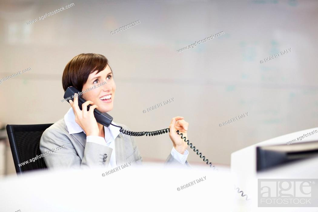 Stock Photo: Smiling businesswoman talking on telephone in office.