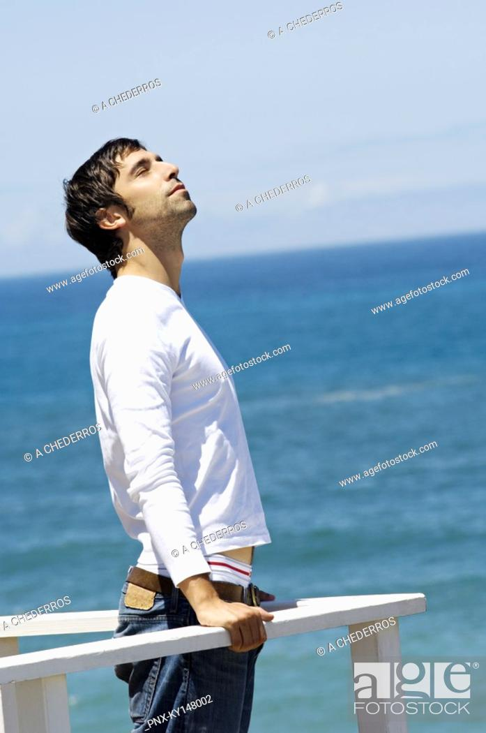 Stock Photo: Young man leaning against balustrade, eyes closed, sea in background.