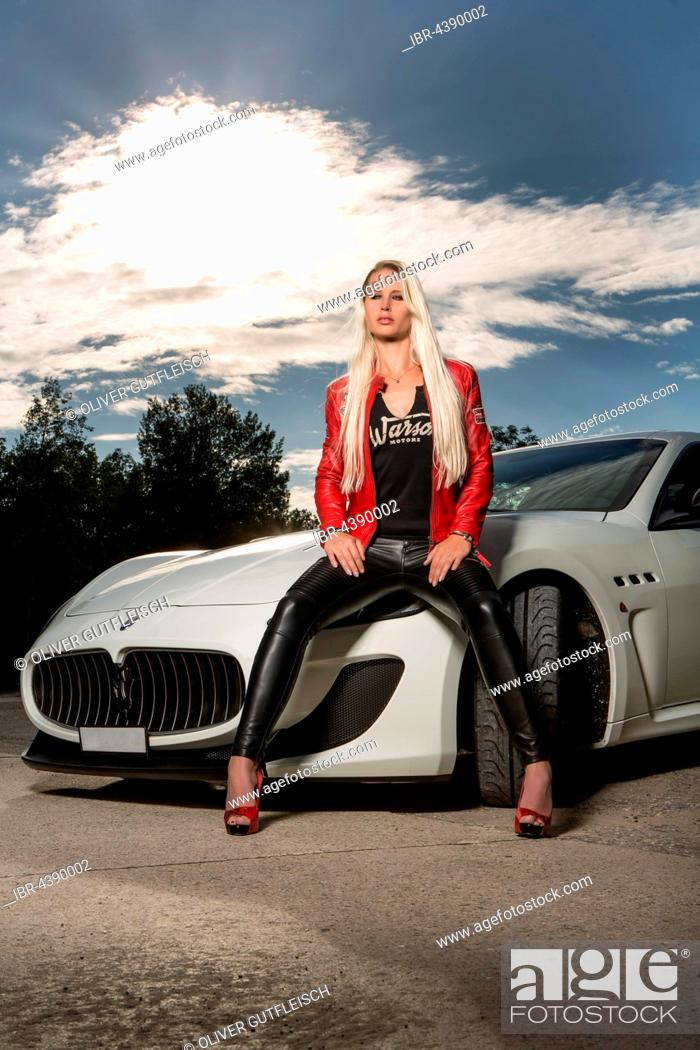Stock Photo: Young woman with long blond hair poses with white Maserati Gran Turismo MC Stradale.