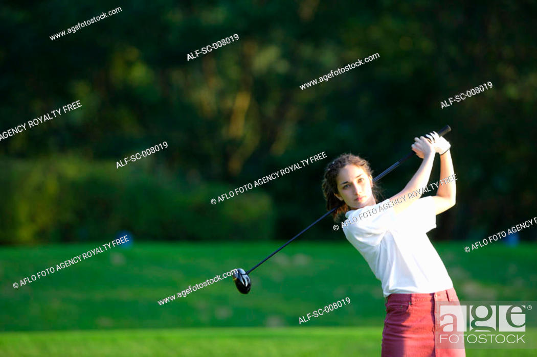 Stock Photo: A young woman makes a stroke with a golf club.
