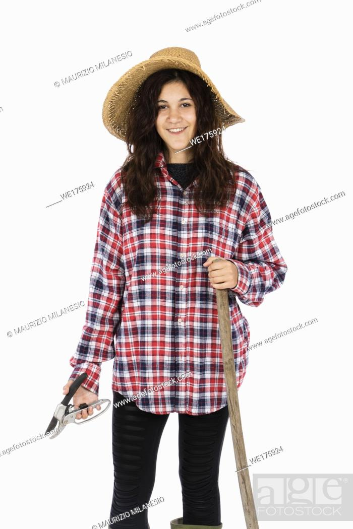 Stock Photo: Young farmer with shears and hoe in hands, she is wearing a straw hat, checked shirt and green rubber boots.