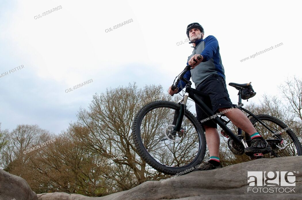 Stock Photo: Mature male mountain biker looking out from rock formation.