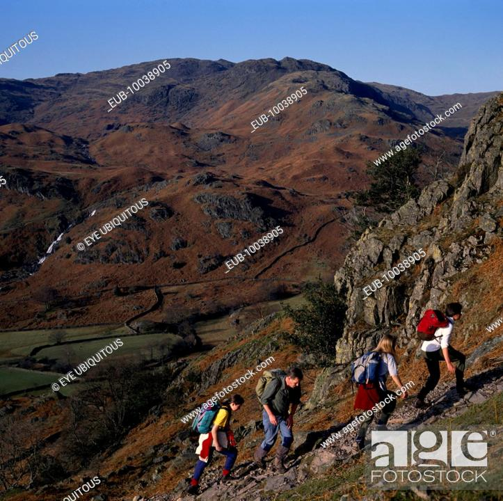 Stock Photo: Walkers on footpath to Helm Crag above Grasmere with view west to Sour Milk Gill.