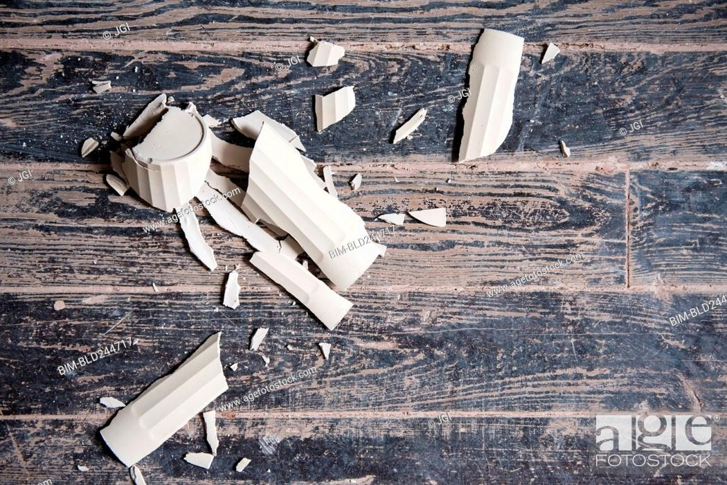 Stock Photo: Broken shards of cup on wooden floor.