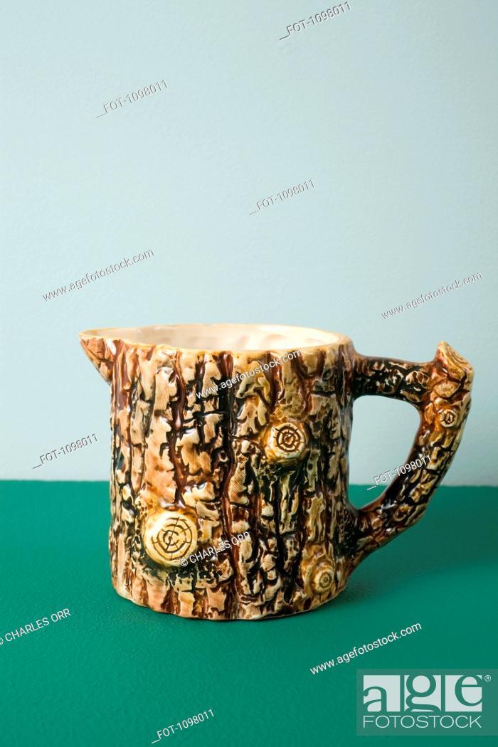 Stock Photo: A ceramic creamer made to look like tree bark.