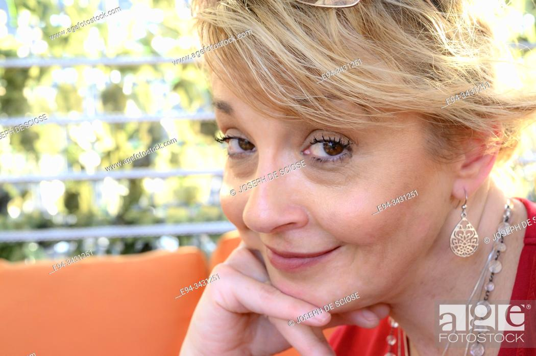 Stock Photo: A 51 year old blond woman with hand on face, smiling at the camera.