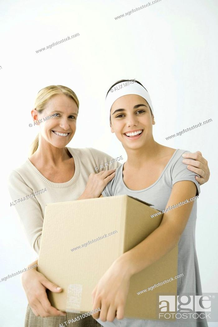 Stock Photo: Young female holding cardboard box, mother holding her shoulders.