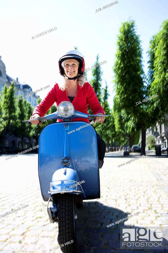 Stock Photo: Woman driving a scooter.