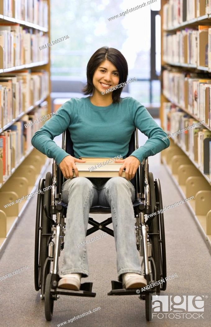 Stock Photo: Mixed Race woman in wheelchair at library.