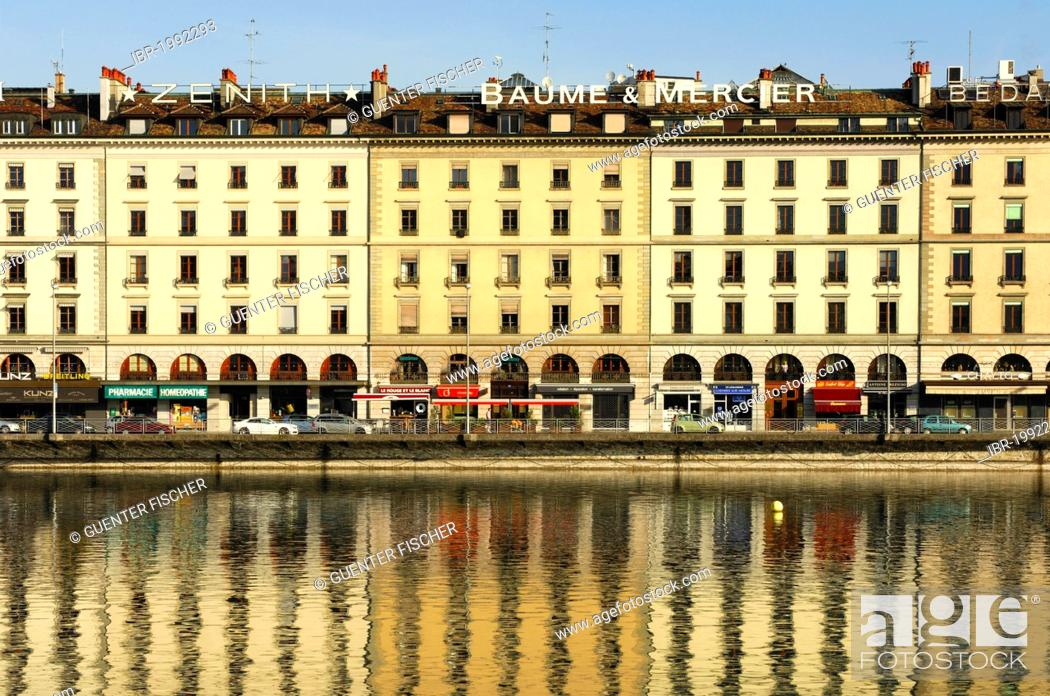 Stock Photo: A row of houses on Quai des Bergues street is being reflected in the water of the Rhone River in downtown Geneva, Switzerland, Europe.