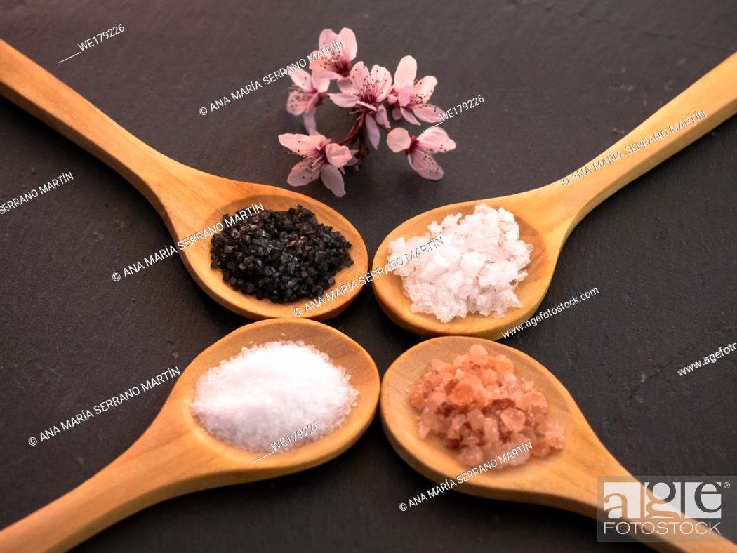 Imagen: Wooden spoons with himalayan salt, black hawaii salt, common salt and salt flakes on a slate plate.