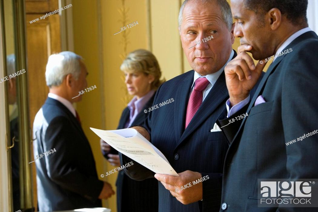 Stock Photo: Mature businessman showing paperwork to colleague, close-up.