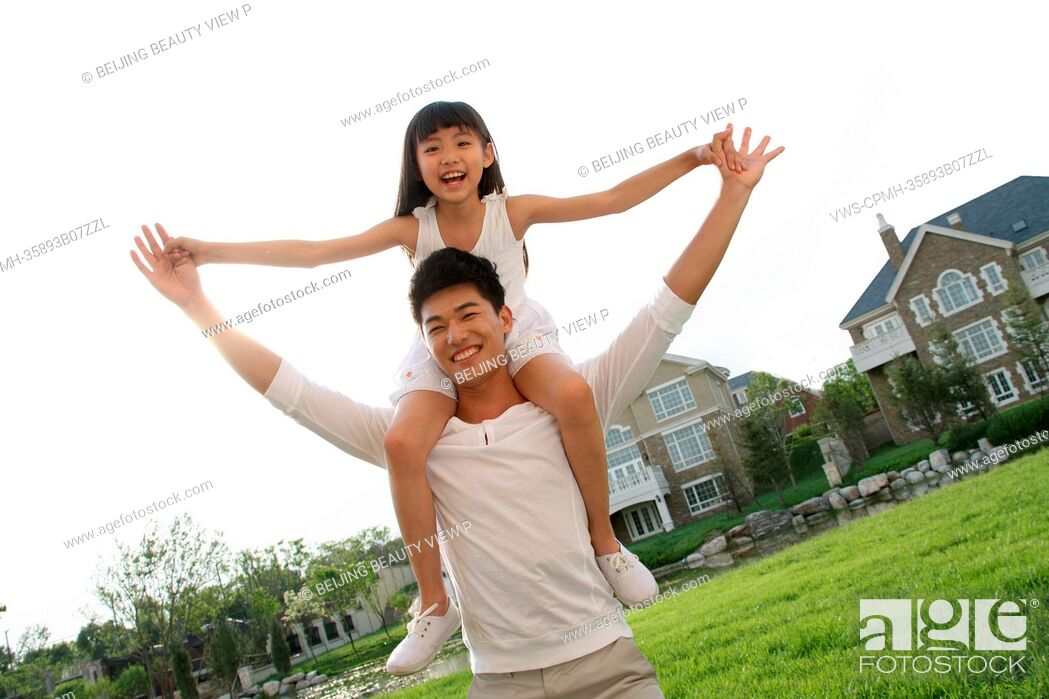 Stock Photo: A girl sitting on father's shoulders on the grass.