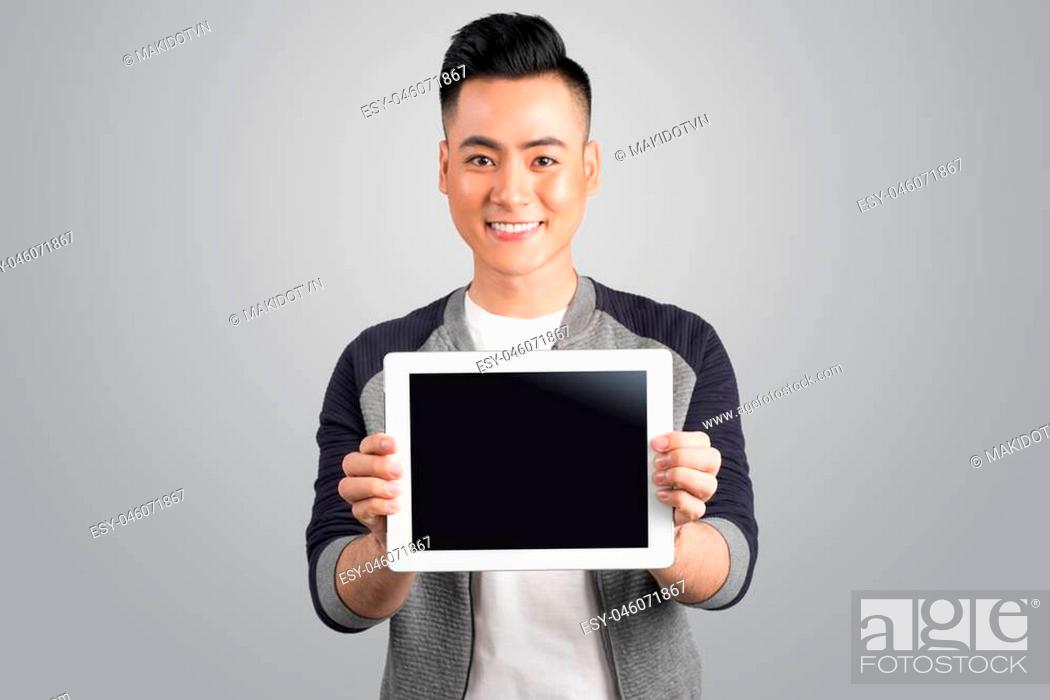 Stock Photo: Confident young asian businessman showing digital tablet screen.