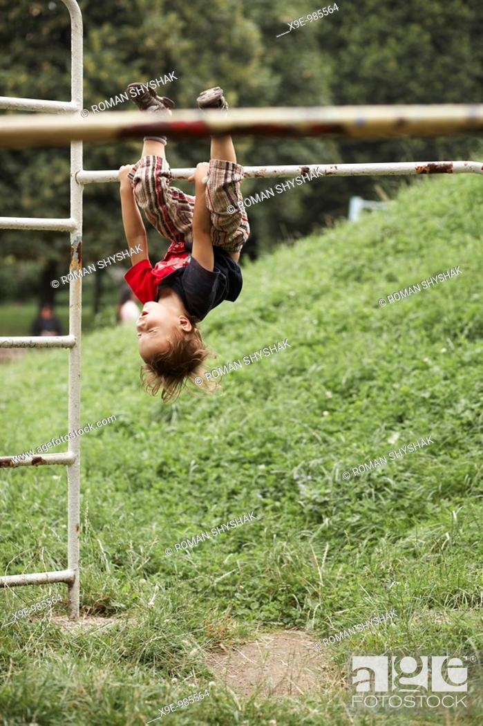 Stock Photo: Little boy hanging upside down from the ladder in the park.
