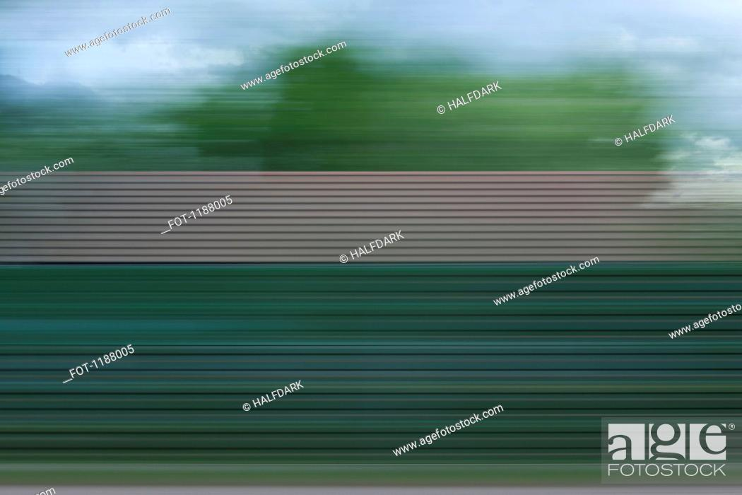 Stock Photo: A building, trees and clouds in abstract blurred pattern viewed from moving train.
