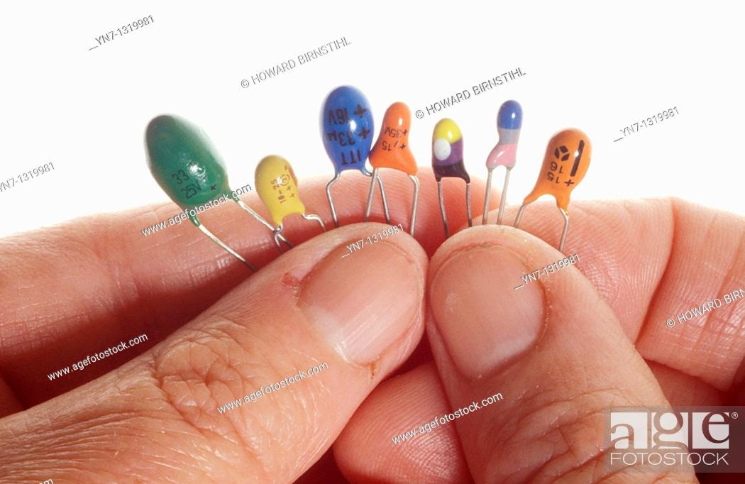Stock Photo: close up of fingers holding a series of diodes.