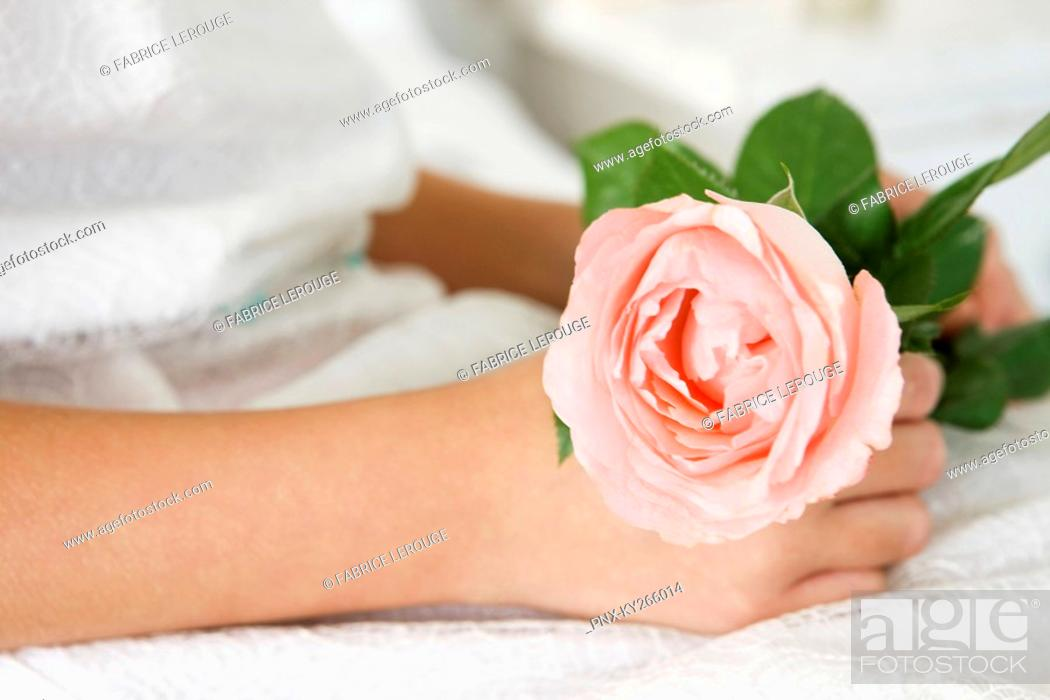 Stock Photo: Close-up of a flower girl holding a flower.
