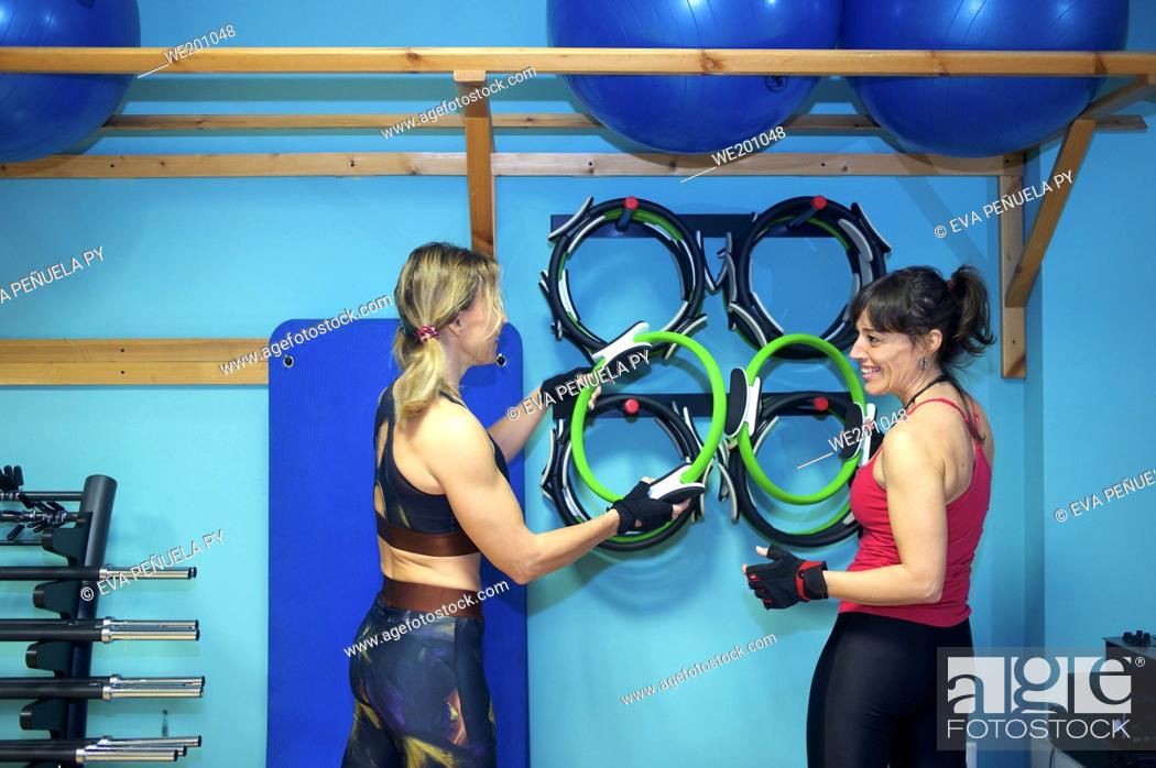 Stock Photo: Two women look at each other and laugh awith extended arms a at the gym. They are also using exercise mats.
