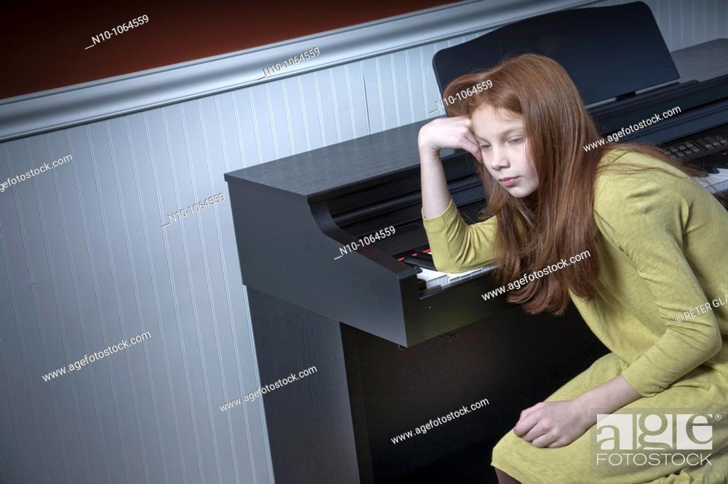 Stock Photo: Preteen redhead girl sitting at an electric piano.