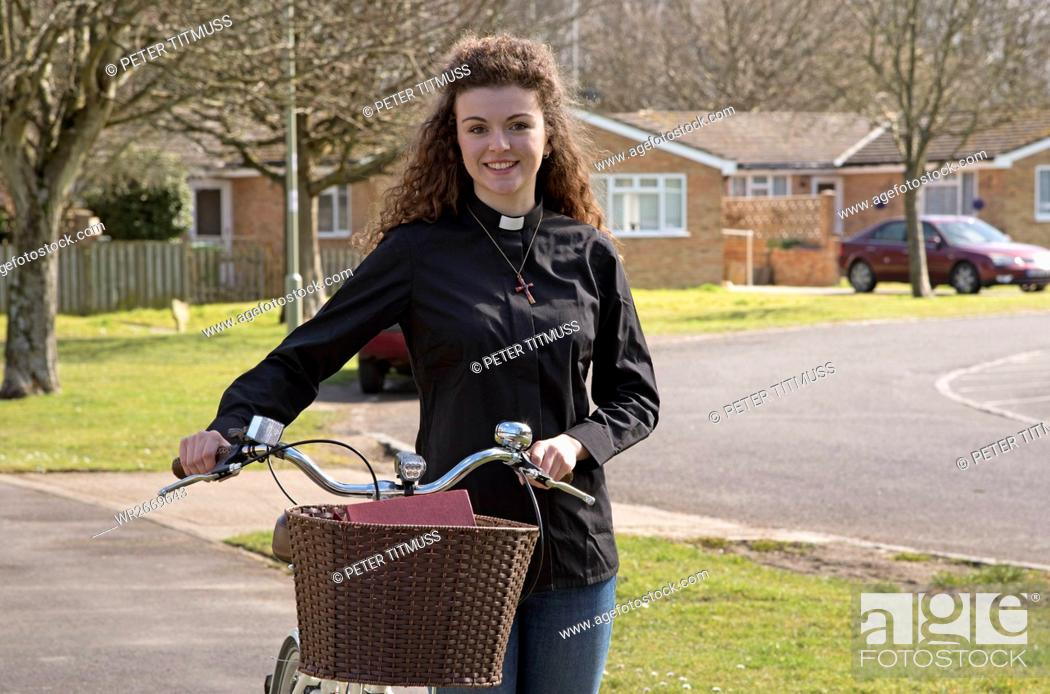 Stock Photo: Young parish priest using a bicycle as transport.