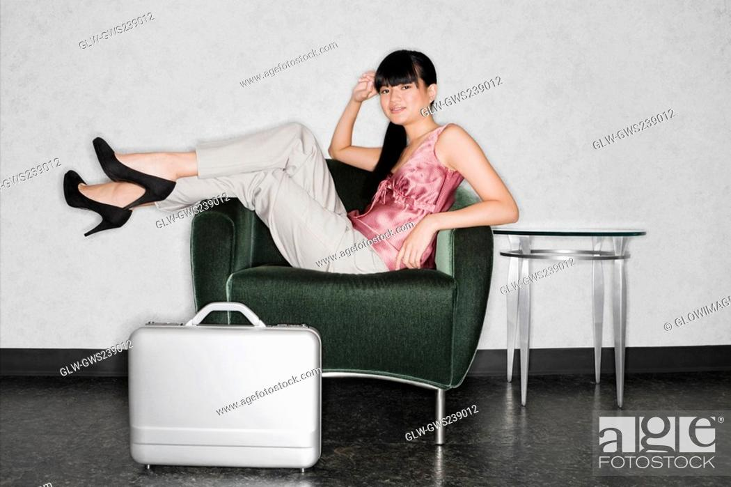 Stock Photo: Young woman sitting in an armchair and smiling.