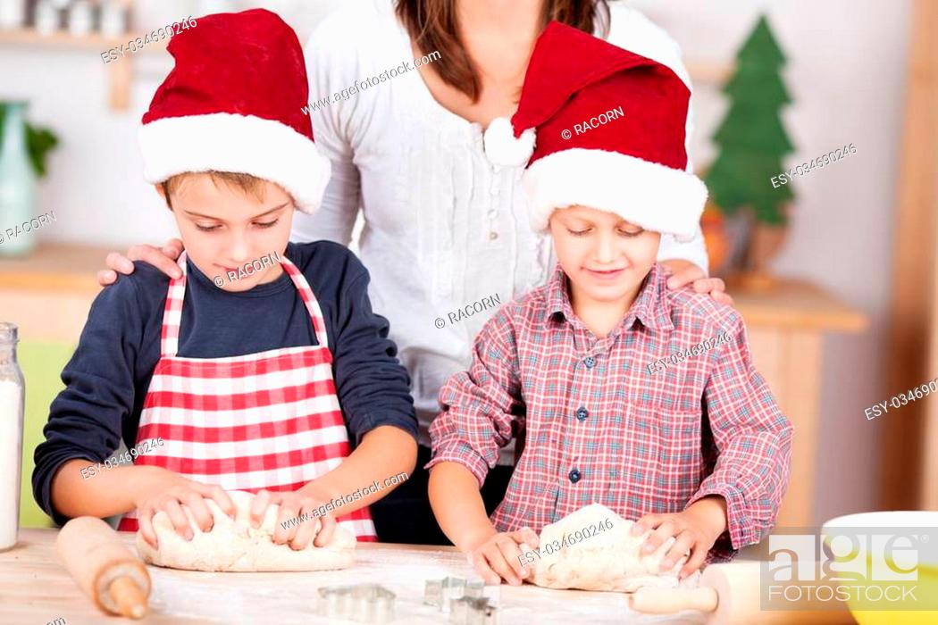 Stock Photo: Two little boys learning to bake Christmas cookies watched by their mother as they stand at the counter in the kitchen in red Santa hats kneading the dough.