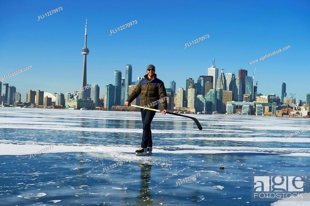 Imagen: Hockey player and city skyline from Ward's Island; Toronto, Ontario, Canada.