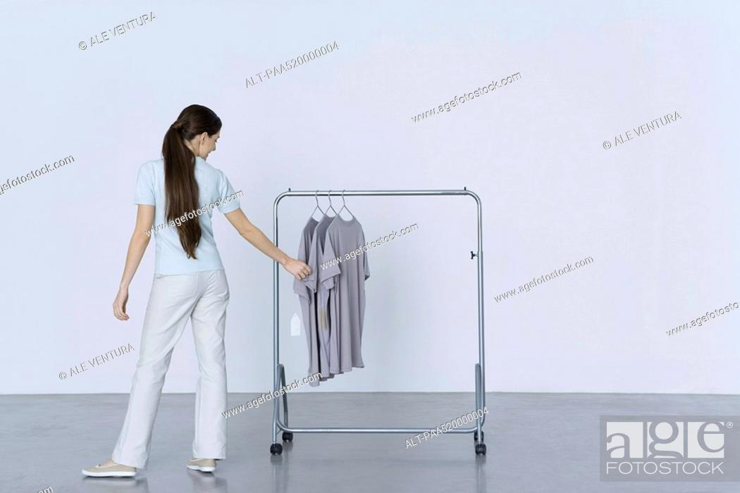 Stock Photo: Woman looking at tee-shirts hanging on rack, rear view.