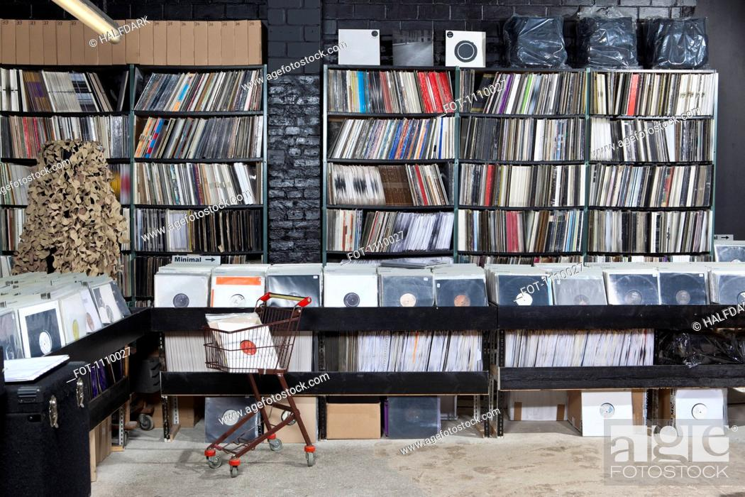 Stock Photo: A shopping cart and rows of records on shelves and in bins at a record store.