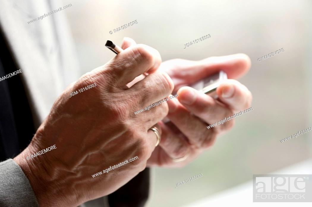 Stock Photo: Close-up of human hands holding mobile phone with touchpad.