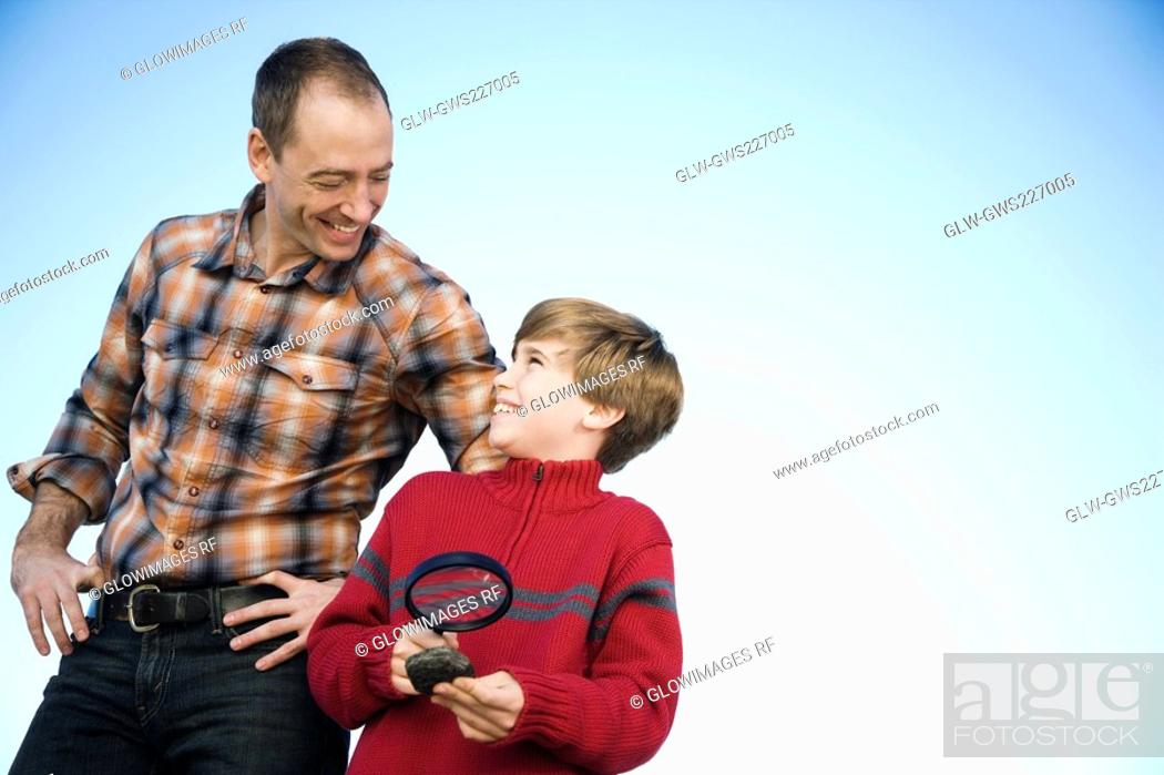 Stock Photo: Boy holding a magnifying glass and standing with his father.