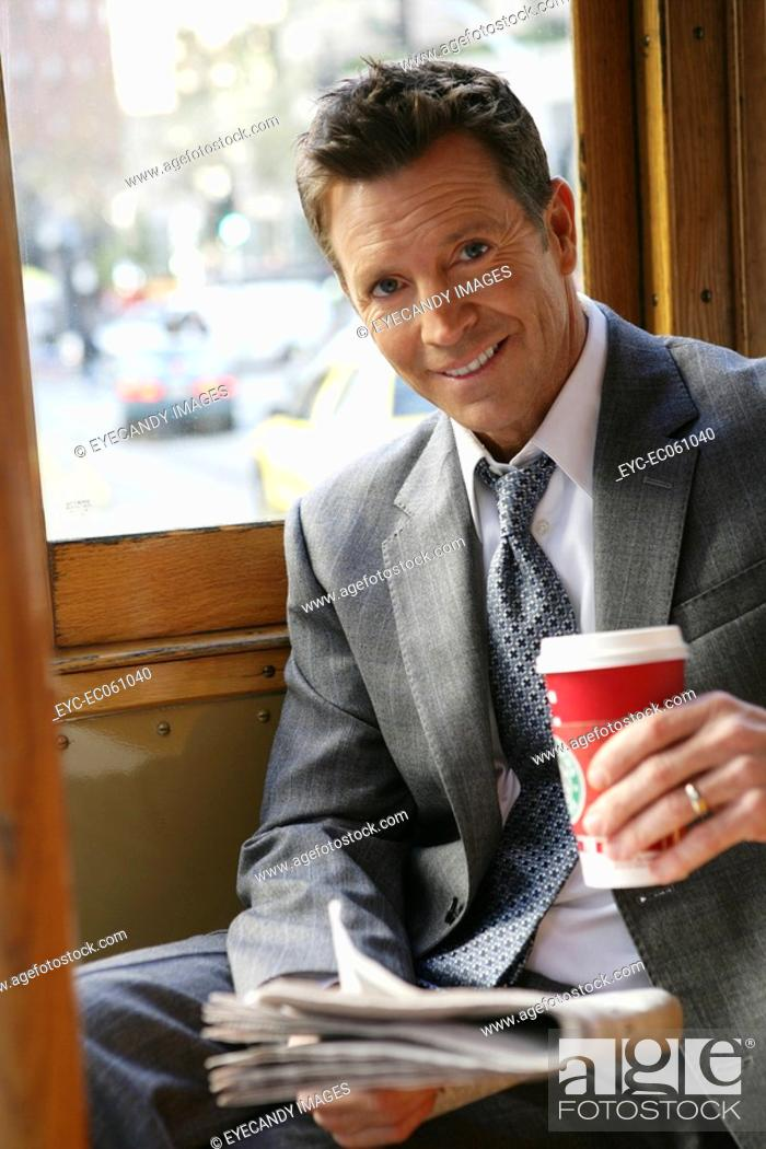 Stock Photo: Mature business man holding a newspaper and take-out cup.