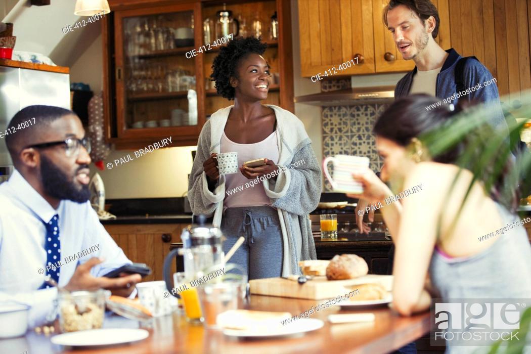 Stock Photo: Friend roommates enjoying breakfast in kitchen.