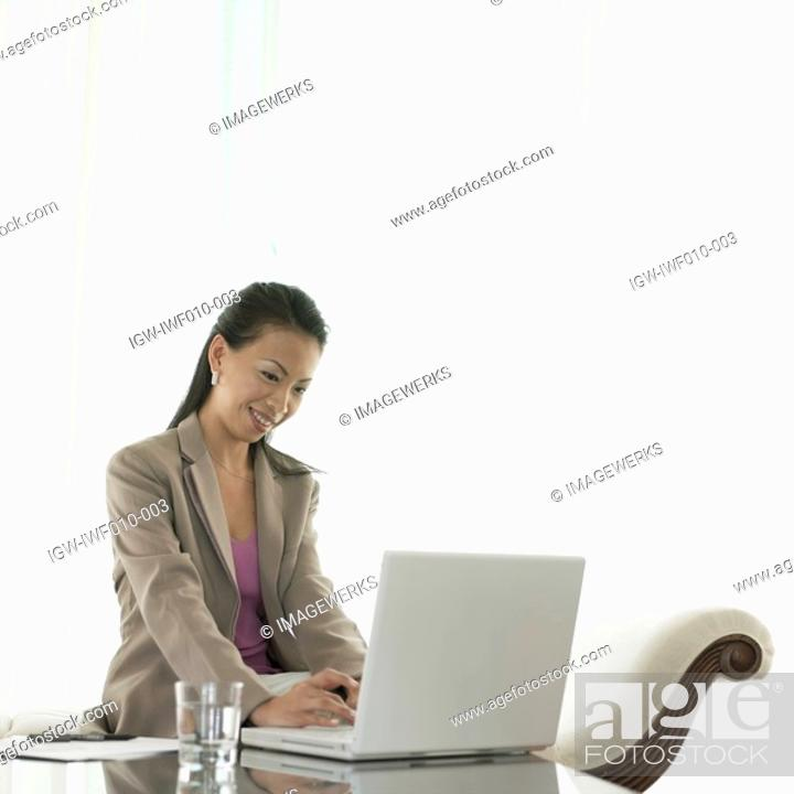 Stock Photo: Businesswoman working on a laptop.