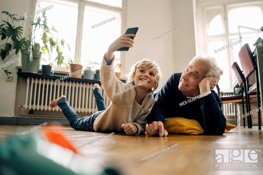 Stock Photo: Grandfather and grandson lying on the floor at home taking a selfie.